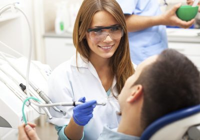 female dentist doing a routine dental cleaning for male patient