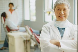 Senior Asian female dentist with assistant and patient in background