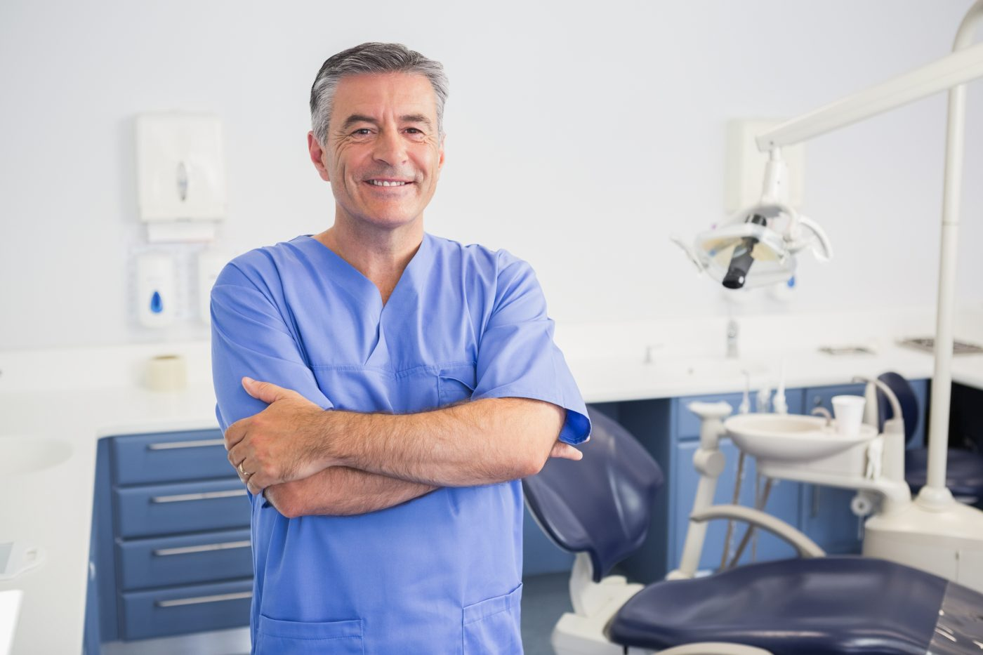 male dentist smiling in front of dental patient room wearing blue scrubs