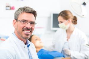 Male dentist smiling with patients in the background