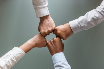 Four people fist bumping